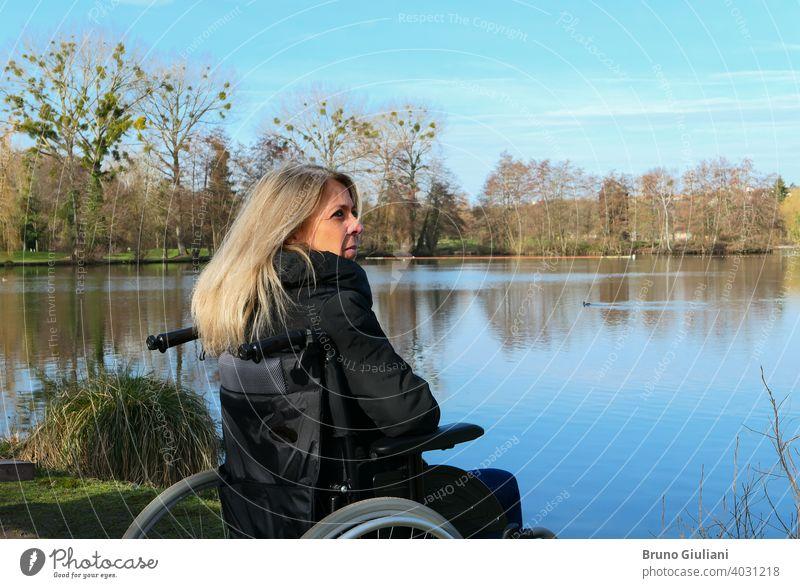 Konzept der behinderten Person. Eine Frau in einem Rollstuhl draußen in der Natur vor einem See. Erwachsener schön blondes Haar Kaukasier Kontemplation