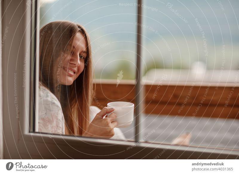 Junge Frau stehend nach dem Duschen am Morgen auf dem Balkon des Hotels. hält eine Tasse Kaffee oder Tee in ihren Händen. Blick nach draußen Natur Wald und Berg