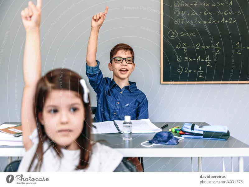 Schüler mit Maske auf dem Tisch heben die Hände in der Schule Junge Handreichung sprechend fragen Coronavirus Klasse teilnehmend Sicherheit Virus neue Normale