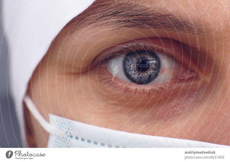 Nahaufnahme des gereizten, roten, blutunterlaufenen, gestressten Auges einer Ärztin bei Coronavirus covid-19. Bedauern, Angst und Verzweiflung. Pandemie und Virus-Epidemie. Konzept der Gesundheit, Krankheit und Behandlung.
