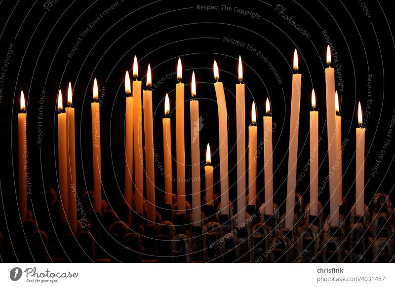 Kerzen in Reihe vor dunklem Hintergrund kerzen licht schatten dunkelheit leuchten helligkeit kirche gottesdienst angst trauer christentum jesus flamme