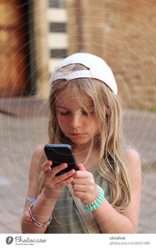 Mädchen mit Kappe schaut auf Handy mädchen kind jugendlich medien konsum gefahr mediengesellschaft sucht handy mobiltelefon elektronik Internet Mobilität