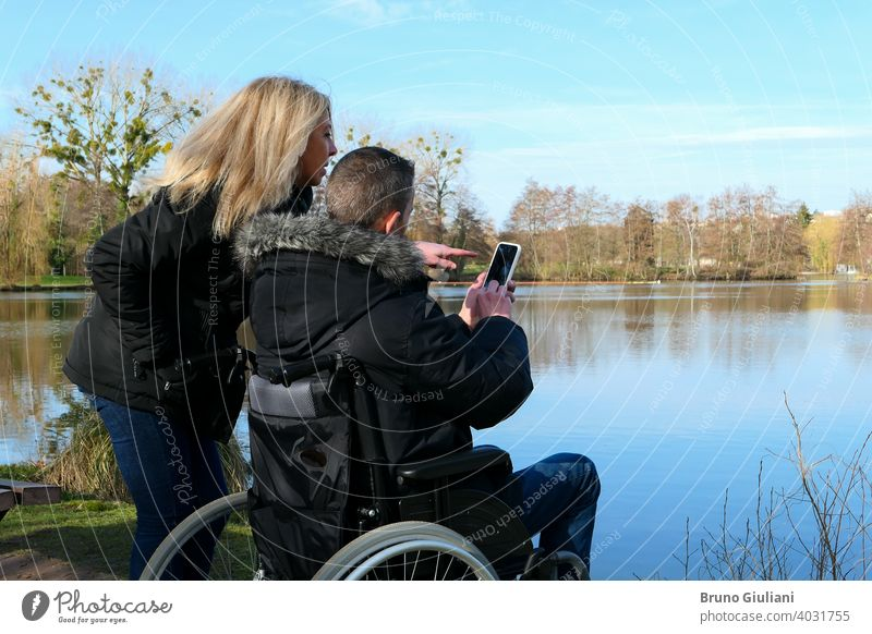 Konzept einer Person mit einer körperlichen Behinderung. Ein Mann in einem Rollstuhl mit einer Frau, die neben ihm steht. Paar, das Technologie verwendet, während es auf ein Smartphone schaut. Ländliche Szene an einem See.