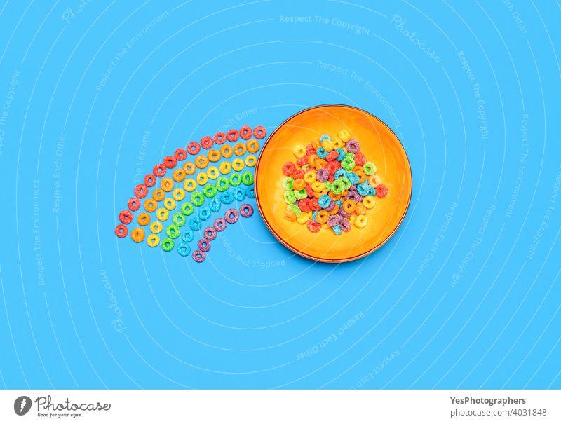Müslischale isoliert auf blauem Hintergrund. Regenbogen-Fruchtgeschmack Ring Cerealien, Ansicht von oben obere Ansicht sortiert Blauer Hintergrund