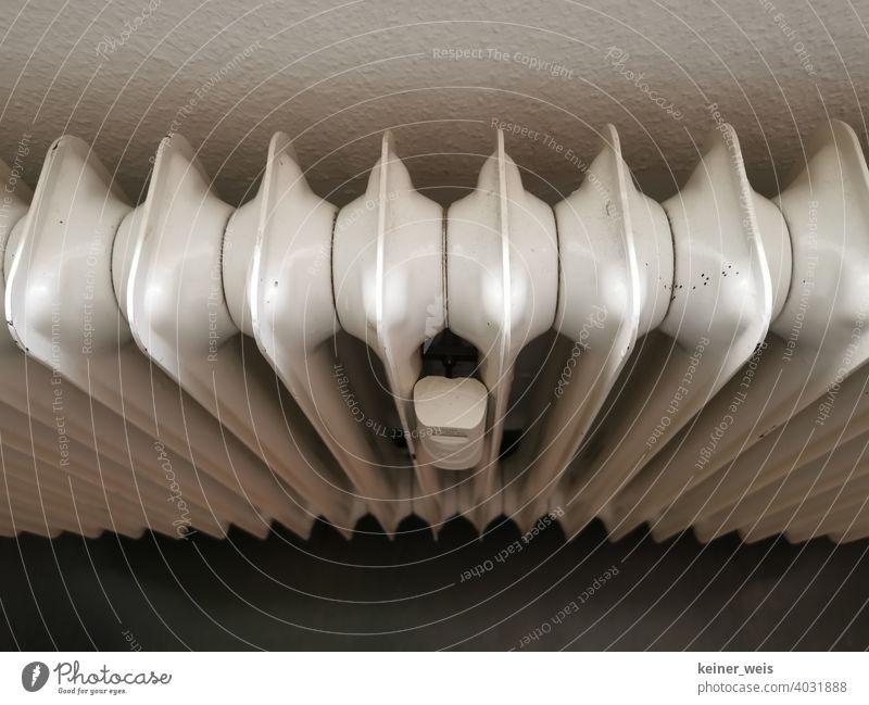 Ein alter Rippenheizkörper oder Radiator mit Verbrauchsmessgerät Heizung Ölheizung Zentralheizung Heizkosten weiß Stahl Eisen Boden Wand indoor Energieverbrauch