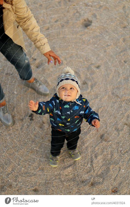 kleines Baby, das unter dem Schutz eines Erwachsenen nach oben schaut Neugier Achtsamkeit Hoffnung Wunschvorstellung Experiment Realität echte Menschen