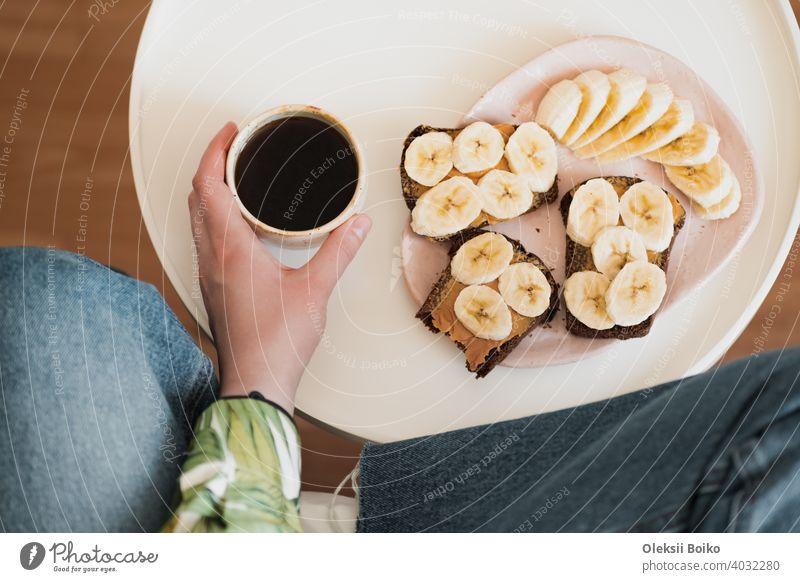 Frau hält eine Tasse schwarzen Kaffee, Schuss direkt über. Mit gesundem Obst und Erdnussbutter-Sandwich zum Frühstück, trinken Morgen Kaffee zu Hause Banane
