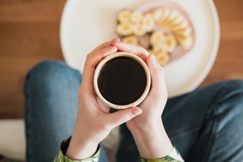 Frau hält eine Tasse mit schwarzem Kaffee, Aufnahme direkt von oben. Beim Frühstück, Morgenkaffee zu Hause trinken schwarzer Kaffee Körperteile Nahaufnahme