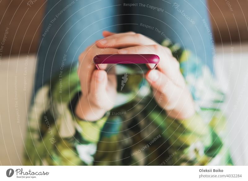 Mobiltelefon in den Händen einer Frau, Aufnahme von oben mit dünner Tiefenschärfe. Weibliche Person hält ein Smartphone in den Händen Hintergrund blanko Browsen