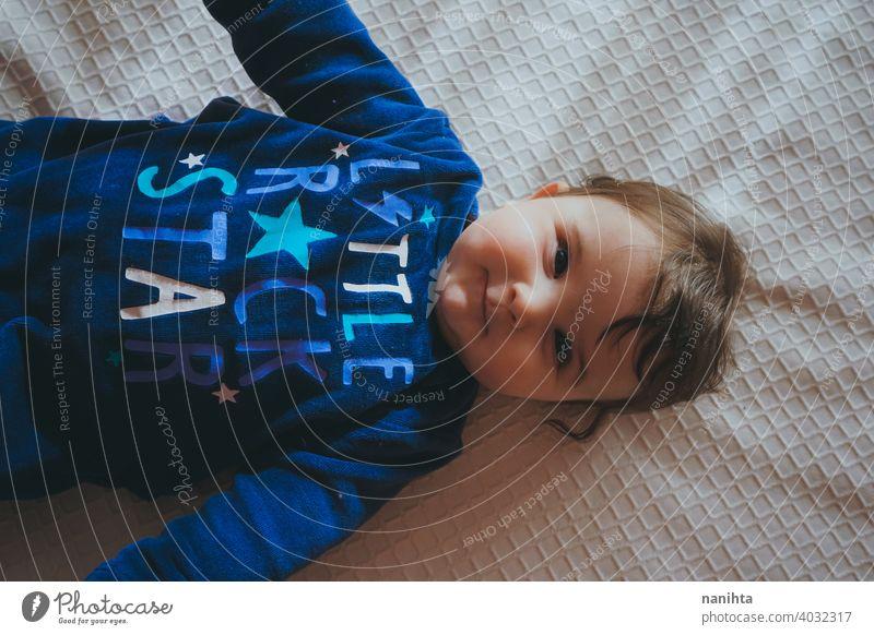 Kleines Baby in Blau liegt auf einem Bett Säuglingsalter niedlich lieblich Mädchen Schlafzimmer heimwärts Familie bezaubernd blau Pyjama spielerisch Gesicht