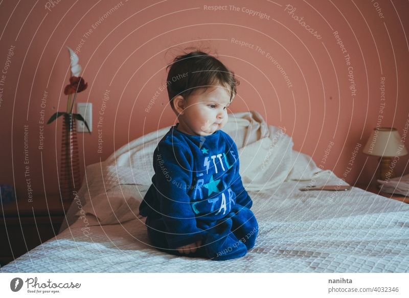 Kleines Baby sitzt auf einem Bett in einem rosa Zimmer sitzen Sitzen Säuglingsalter niedlich bezaubernd lieblich Pyjama blau Europäer Kaukasier heimwärts