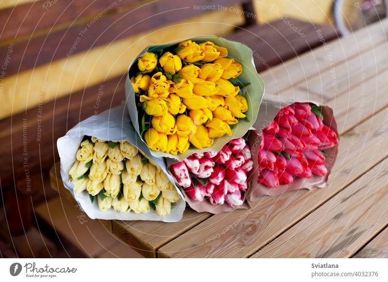 Mehrere Sträuße von Tulpen in verschiedenen Farben in Papierverpackung liegen auf einem Holztisch. Frauentag, Muttertag, Valentinstag. Ein Geschenk, Grußkarte, Platz für Text