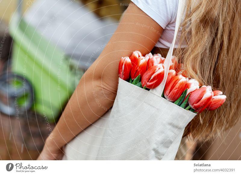 Nahaufnahme eines Blumenstraußes aus Tulpen in einer Stofftasche auf der Schulter eines Mädchens. Geschenk für Frauentag, Valentinstag, Muttertag Glück