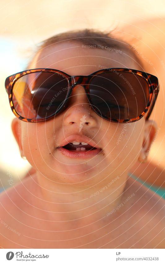glückliches Kind mit Sonnenbrille und Blick in die Kamera Sommer Freude Freizeit Urlaub süß Lächeln außerhalb Lachen freudig Feiertag Gesundheit Glück Freiheit