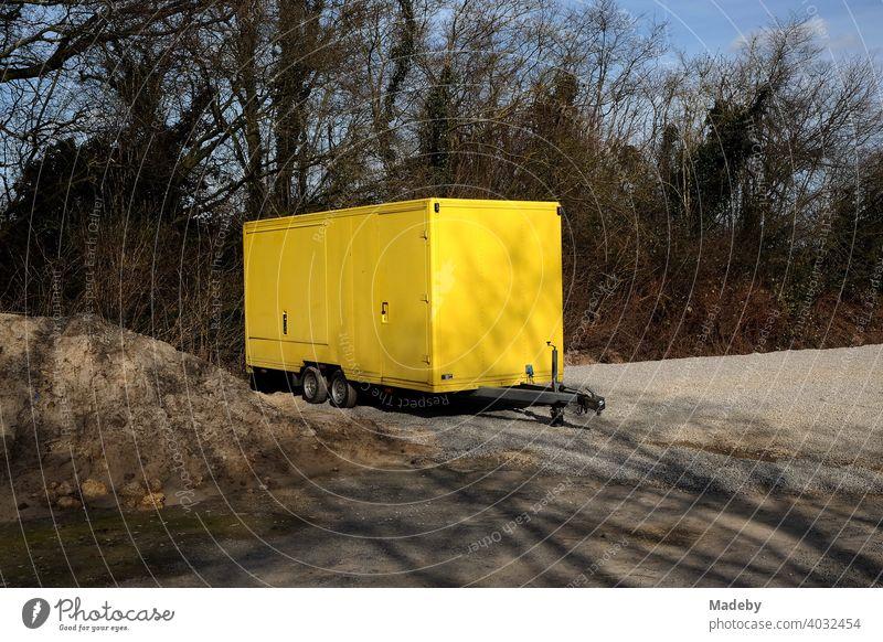 Tandemanhänger mit leuchtend gelbem Aufbau auf einem einsamen Schotterparkplatz in Lemgo in Ostwestfalen-Lippe Anhänger Verkaufsstand Gelb Knallgelb Imbiss