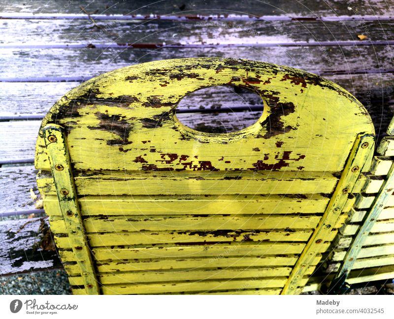 Vergilbter gelber Klappstuhl aus Holz vor einem Café in Bielefeld im Teutoburger Wald in Ostwestfalen-Lippe Stuhl Holzstuhl Gelb Morbide Alt heruntergekommen