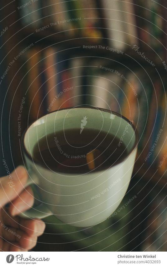 Teetasse mit schwarzem Tee und Zitrone in einer Hand, dahinter unscharf ein Bücherregal Darjeeling Winter Teebecher aufwärmen kälte Frühstück heiß Pause