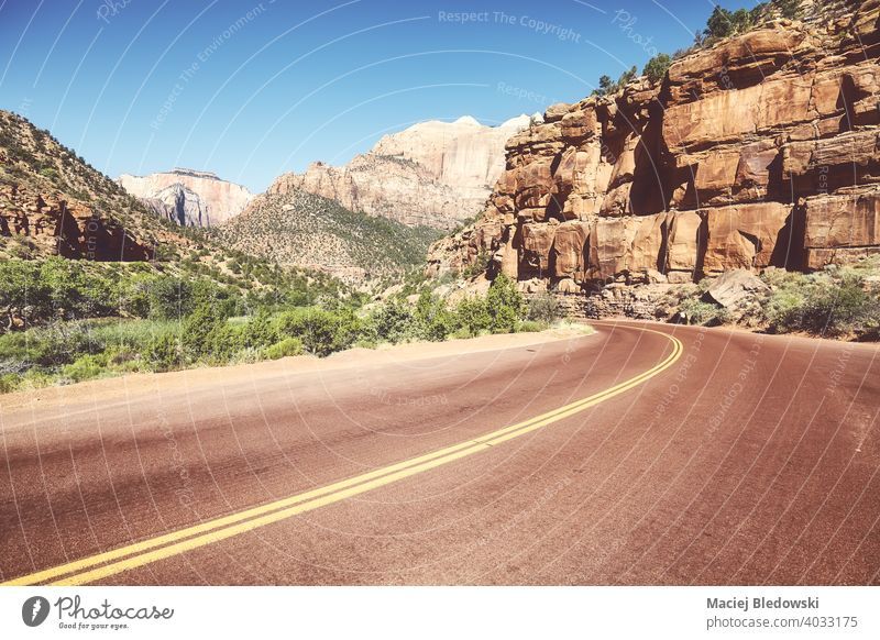 Asphaltstraße im Zion National Park, Retro-Farbtonung angewendet, Utah, USA. Straße Autobahn leer Tal reisen Ausflug retro Natur Landschaft Berge u. Gebirge