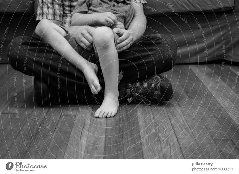 Vater und Sohn sitzen auf Hartholzboden; Kind auf Papas Schoß Kindheit alleinerziehend binden Runde kuscheln Junge Komfort Hände Fuß Zehen Vaterschaft Böden