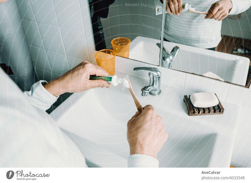 Eine Frau trägt Zahncreme auf seine Bambuszahnbürste auf Zahnbürste Gesundheit Pflege Mund Bad weiß Lebensalter dental älter reif Senior Person Lächeln gealtert