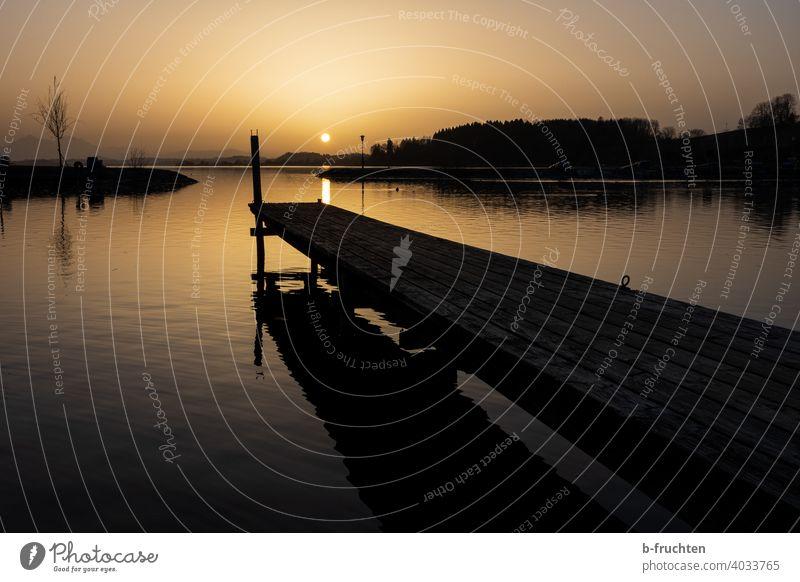 kleiner Holzsteg in der Abendsonne Sonnenuntergang Abendstimmung Himmel Außenaufnahme Abenddämmerung Dämmerung Natur Landschaft Menschenleer ruhig Silhouette