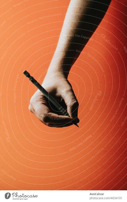 Eine junge Hand, die einen Druckbleistift über einen orangefarbenen Hintergrund mit tiefen Schatten ergreift Bleistift Büro Design Schreibstift Papier Bildung