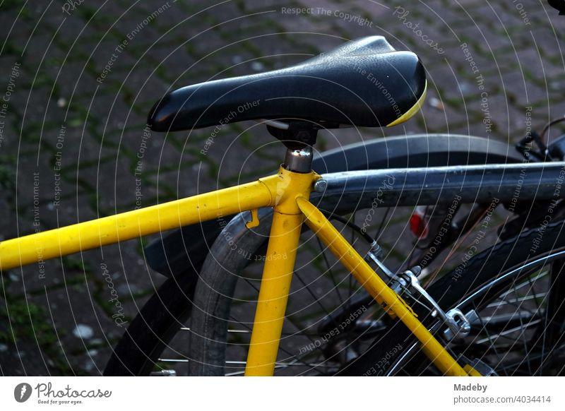 Rennrad mit gelbem Rahmen und schmalem Sattel am Abend an der Hanauer Landstraße im Ostend von Frankfurt am Main in Hessen Fahrrad Rad Gelb Leuchtfarbe Rahmenb