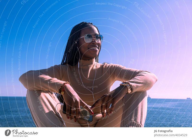 Closeup-Porträt von jungen schwarzen afro Mädchen lächelnd mit Kopfhörer und blauen Himmel Hintergrund, hübsch afro Mädchen Übertragung Positivität und Frieden.