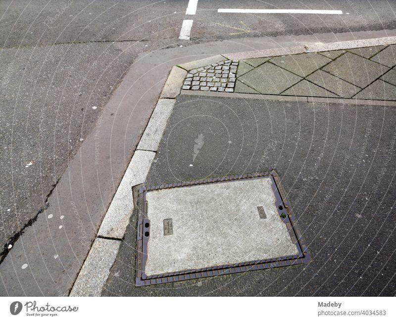Straßenecke mit Bordstein, Asphalt und verschiedenen grauen Pflastersteinen in Frankfurt am Main in Hessen Kreuzung Gully Gullydeckel Kanalisation Grau Grautöne