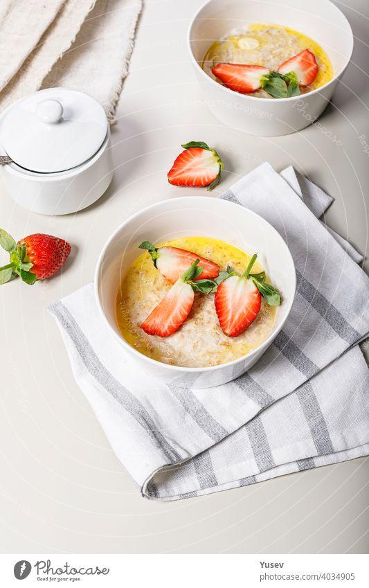 Klassische Haferflocken mit Butter und frischem Obst. Süße Erdbeeren. Leckeres und gesundes Frühstück. Essen Stillleben auf einem hellen Hintergrund. Ideen und Rezepte für Hausmannskost. Vertikale Aufnahme