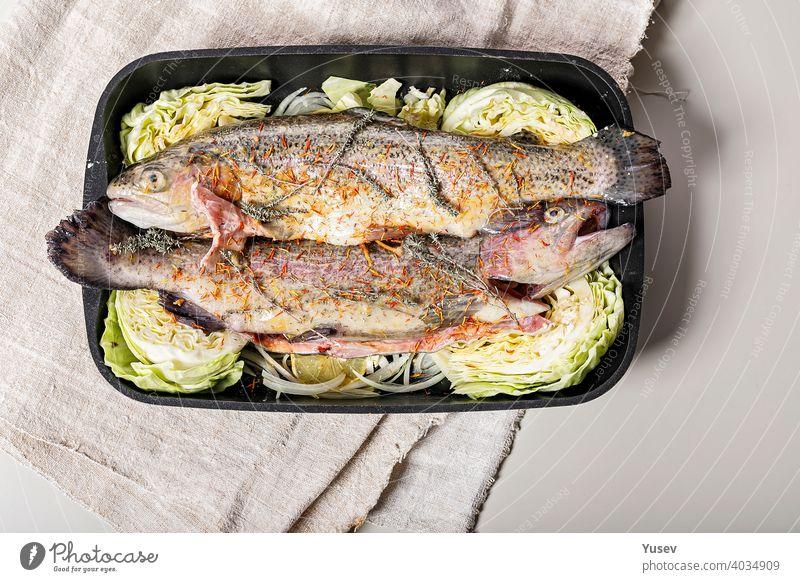 Frische Forelle mit Gewürzen und Gemüse. Süßwasserfisch mit Safran, roten Zwiebeln und Kraut in einer gusseisernen Auflaufform. Heller Hintergrund. Ansicht von oben. Platz zum Kopieren