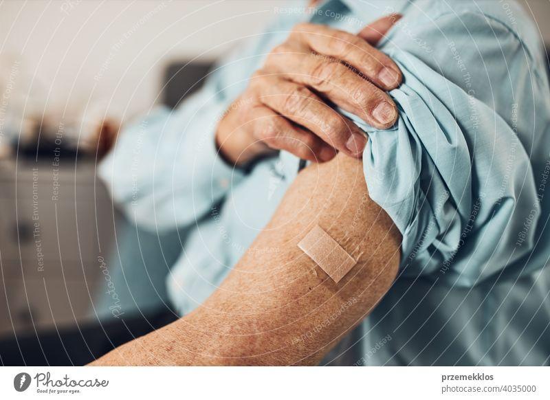 Älterer männlicher Patient, der den Hemdsärmel mit einem Pflaster anstelle einer Impfstoffinjektion hochhält. Impfung gegen Covid-19 oder Coronavirus geduldig