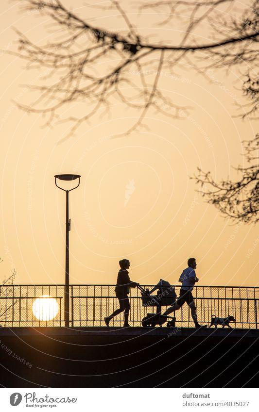 Gegenlichtaufnahme von Familie bei Sonnenuntergang Silhouette joggen laufen Saharasand Joggen Sport Fitness Bewegung Kinderwagen Sonnenlicht Gesundheit