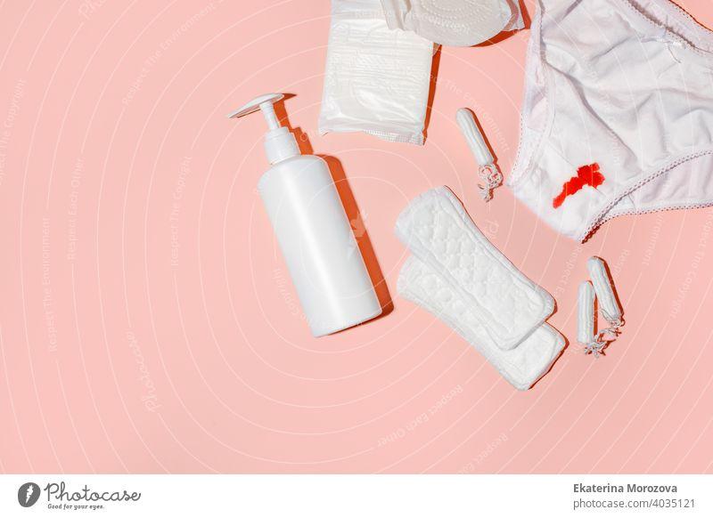 Mädchen, Frauen intime Menstruation Tabu-Konzept - Hose mit rotem Blut, Damenbinden, täglich Binden, intime Seife, Tampon auf rosa Hintergrund. Konzept der monatlichen weiblichen Routine, harter Schatten