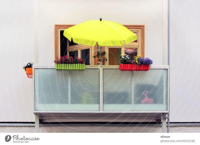 Balkon mit gelbem Sonnenschirm und verschieden farbigen Plastik- Blumenkästen in denen Blumen blühen / Farbe / Urlaub auf Balkonien wohnen Balkonkästen bunt