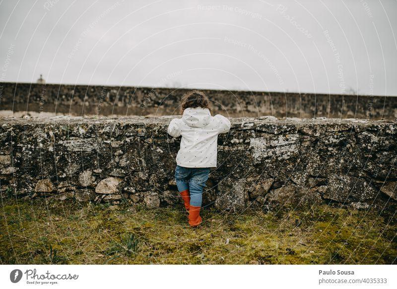 Rückansicht Kind schaut durch Wände Kindheit Kaukasier 1-3 Jahre Farbfoto Textfreiraum Mensch Lifestyle Kleinkind Freude Leben Freizeit & Hobby mehrfarbig