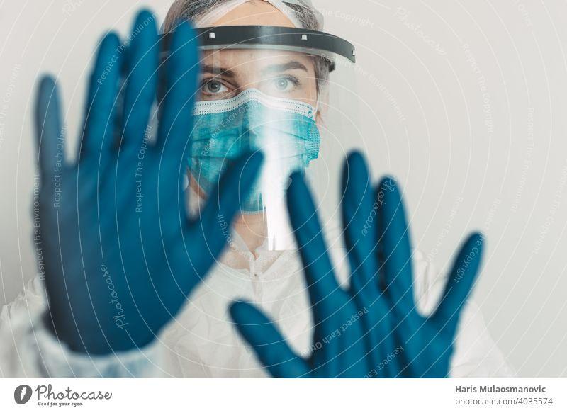 Mitarbeiter im Gesundheitswesen mit Schild und Maske zeigt Stopp-Geste Kur Krankheit Arzt England Seuche Experiment Frankreich Deutschland Handschuhe