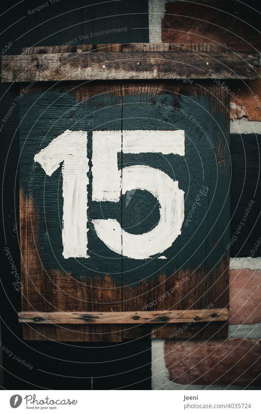 Hausnummer fünfzehn geschrieben als Zahl 15 auf einem rustikalen Holzbrett mit weißer Farbe auf dunklem Hintergrund Ziffern & Zahlen ziffer Ziffern und Zahlen