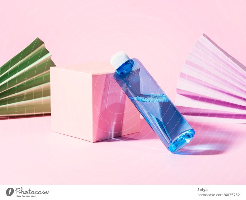 Blaue Hautpflege Toner Flasche auf rosa geometrischen Hintergrund mizellar Pflege Schönheit Anzeige generisch Kosmetik Gesichtsbehandlung Produkt