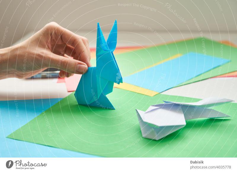 DIY-Konzept. Frau machen Origami Ostern Kaninchen aus Farbe Papier. Origami Unterricht Hase Prozess Hand Hobby handgefertigt Kunst Handwerk Hintergrund