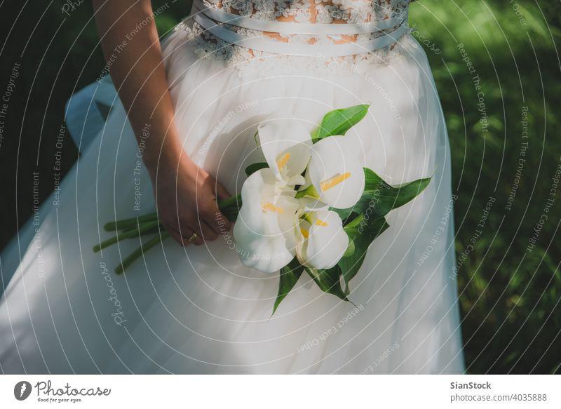 Junge schöne Braut hält einen Blumenstrauß. Hochzeit Kleid weiß Schönheit Frau Mädchen jung hochzeitlich Natur Bäume Feier Liebe Eleganz Hintergrund Glück Farbe