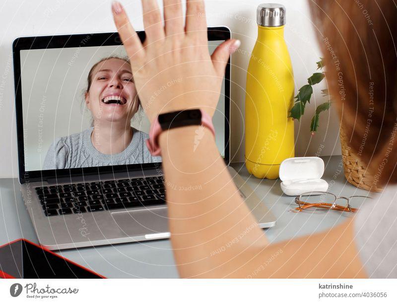 Zwei Freunde trinken Wein, während sie einen Videoanruf führen Frauen Laptop Isolation sozial Distanzierung soziale Distanzierung zwei Anruf Lächeln Lachen grau
