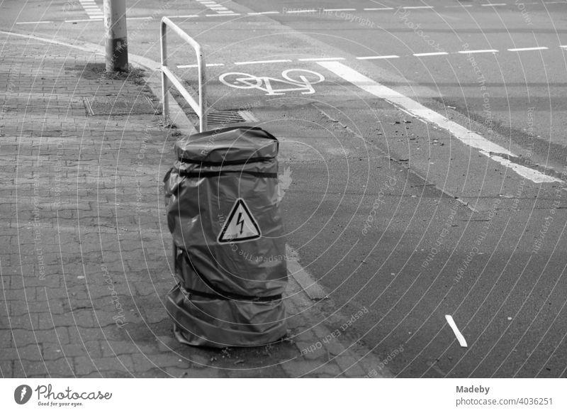 Warnung vor Hochspannung an einem mit Folie umwickelten Pfeiler zwischen Bürgersteig und Radweg im Westend von Frankfurt am Main in Hessen, fotografiert in neorealistischem Schwarzweiß