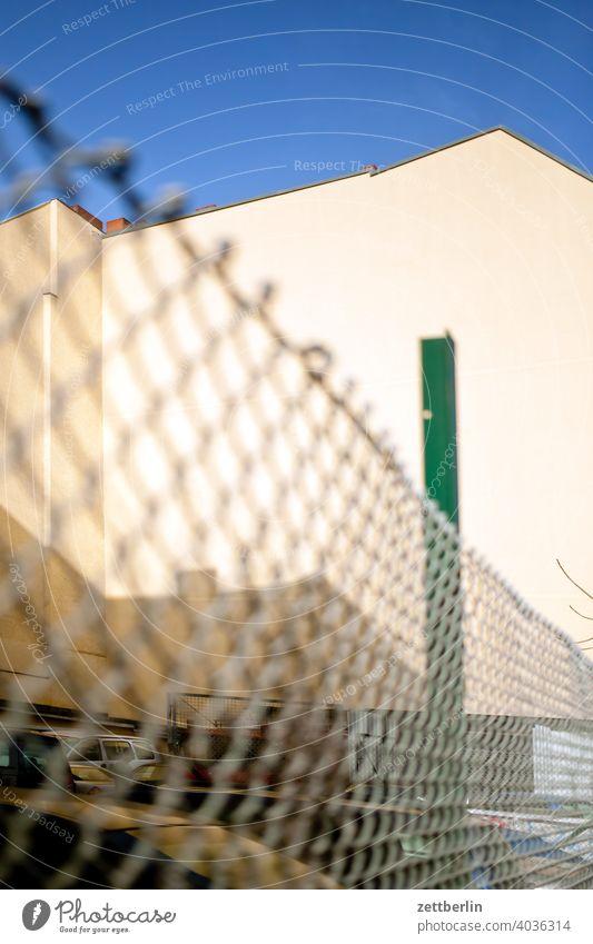 Maschendrahtzaun mit Hinterhoffassade altbau außen brandmauer haus himmel himmelblau hinterhaus hinterhof innenhof innenstadt mehrfamilienhaus menschenleer