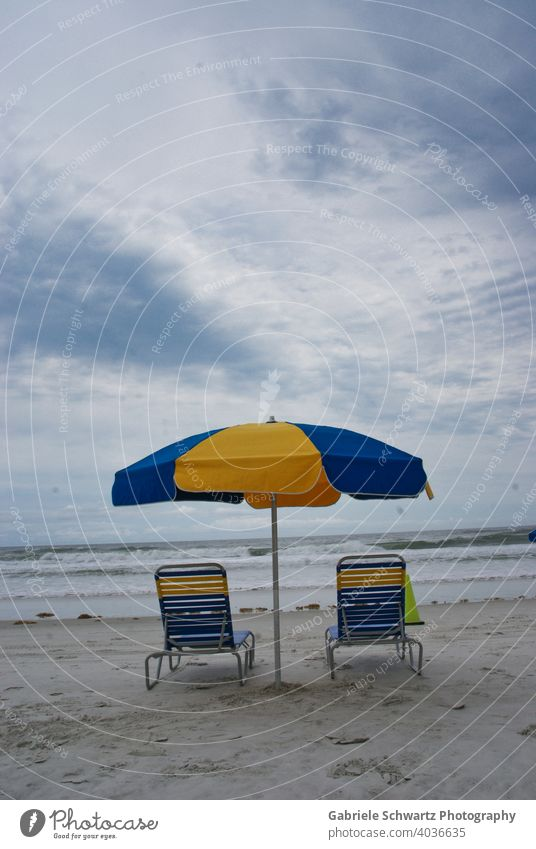 Einsame Liegestühle am Meer Liegestuhl Strand leer Wellen Wellengang Gischt Sand Sandstrand Streifen gestreift blau gelb Sonnenschirm Seetang Wolken