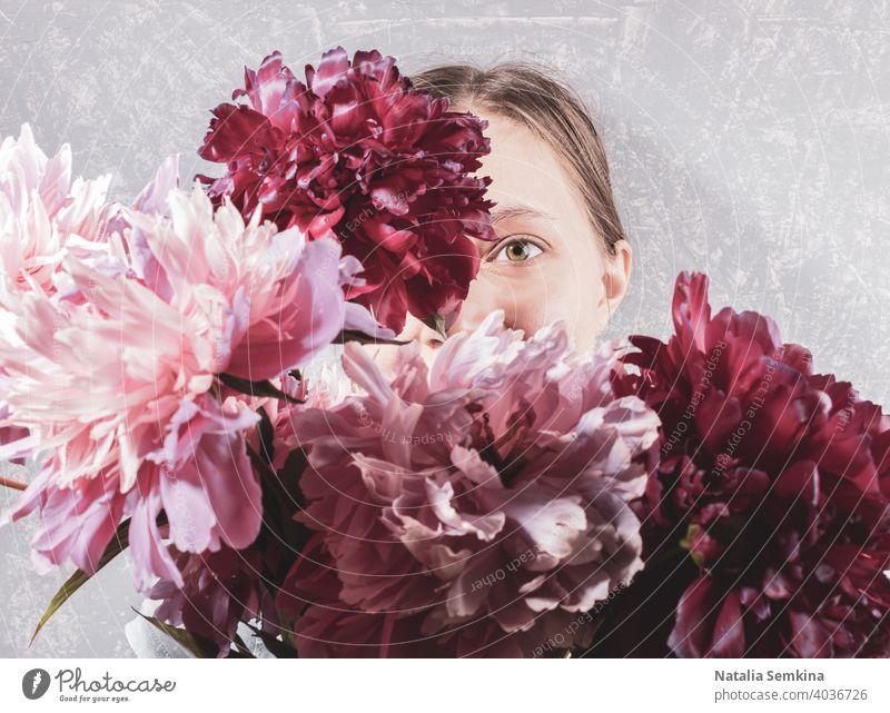 Große unscharfe Bouquet von rosa Pfingstrosen Abdeckung Gesicht junge Frau auf grauem Hintergrund. Fokus sind auf einem ihr Auge. kreativ retro gesichtslos