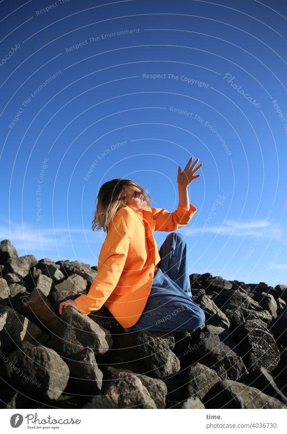 Lara frau jacke wellenbrecher steine himmel sitzen hand schutz sonnig jeans aufstützen abstützen wolken