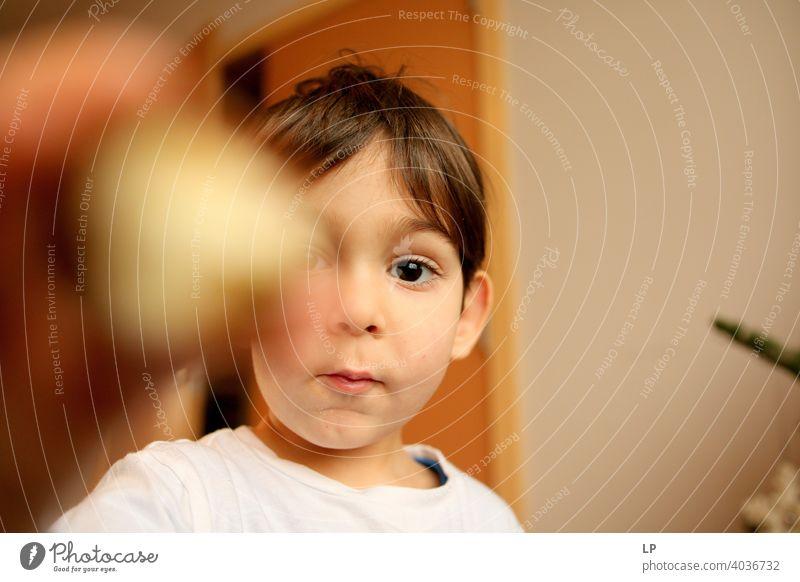 schönes Kind, das sehr ernst in die Kamera schaut und etwas zeigt verwirrt ratlos skeptisch Skepsis Zweifel hestitate Unsicherheit Kindheit Realität Experiment