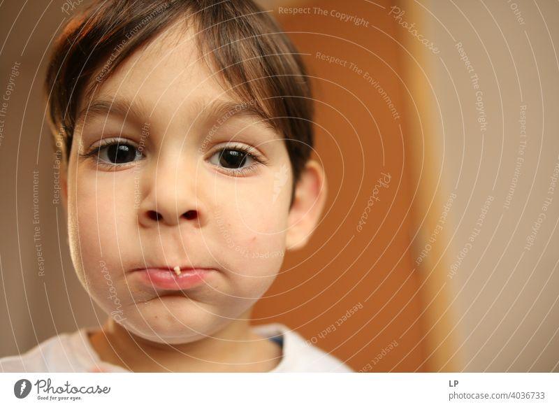 schönes Kind schaut sehr ernst in die Kamera, isst etwas verwirrt ratlos skeptisch Skepsis Zweifel hestitate Unsicherheit Verwirrung Kindheit Realität