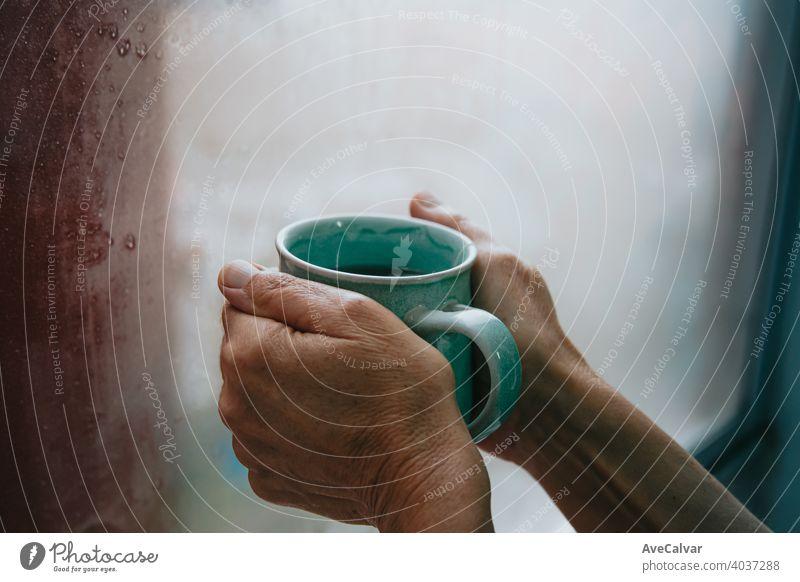 Zwei alte Hände, die einen schnellen Tee während eines kalten Tages greifenZwei alte Hände, die einen schnellen Tee während eines kalten Tages greifen trinken